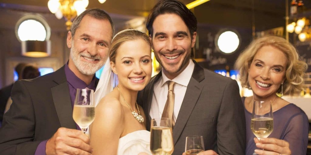 Portrait of happy bride and groom toasting champagne flutes with parents