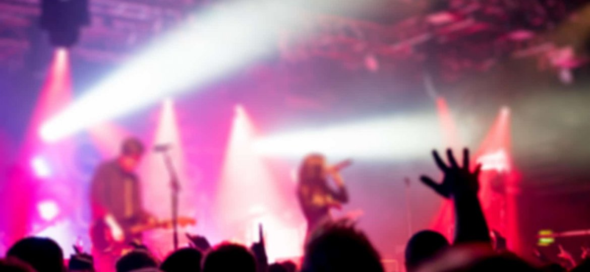 Blurred background, Bokeh, silhouette of cheering audience, hands up and musicians on the stage with lighting in indoor concert
