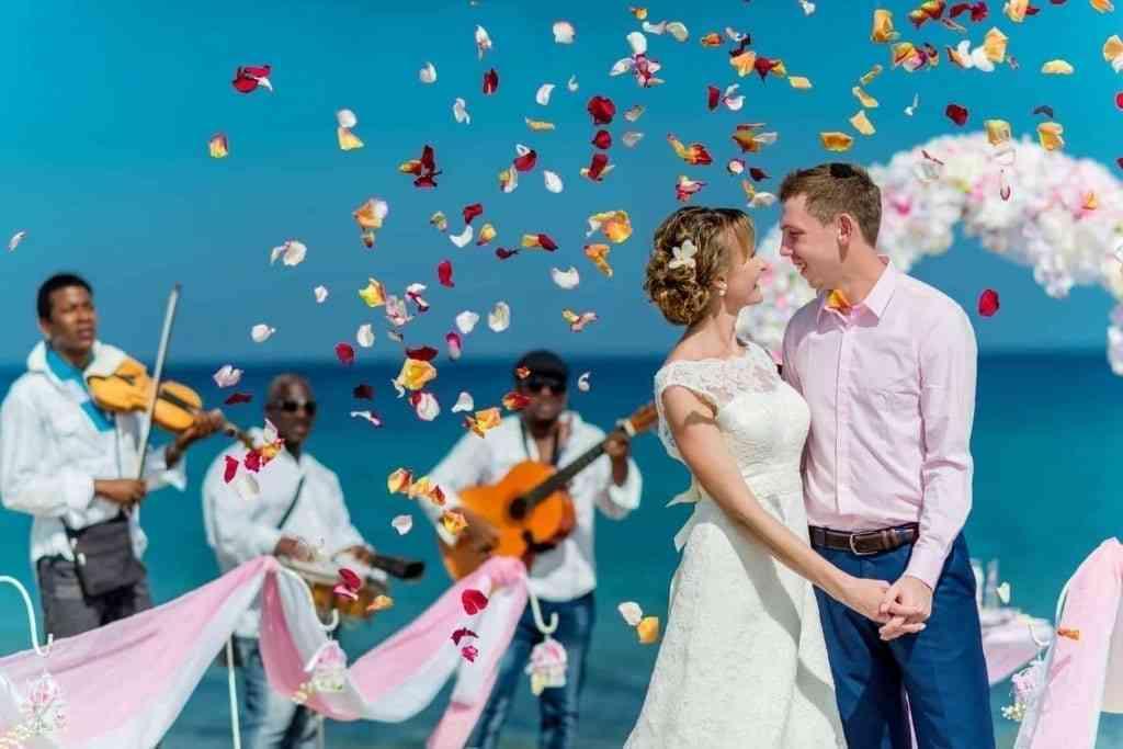 A wedding couple on a sunny beach near the arch and musicians