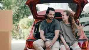 Couple sitting on car