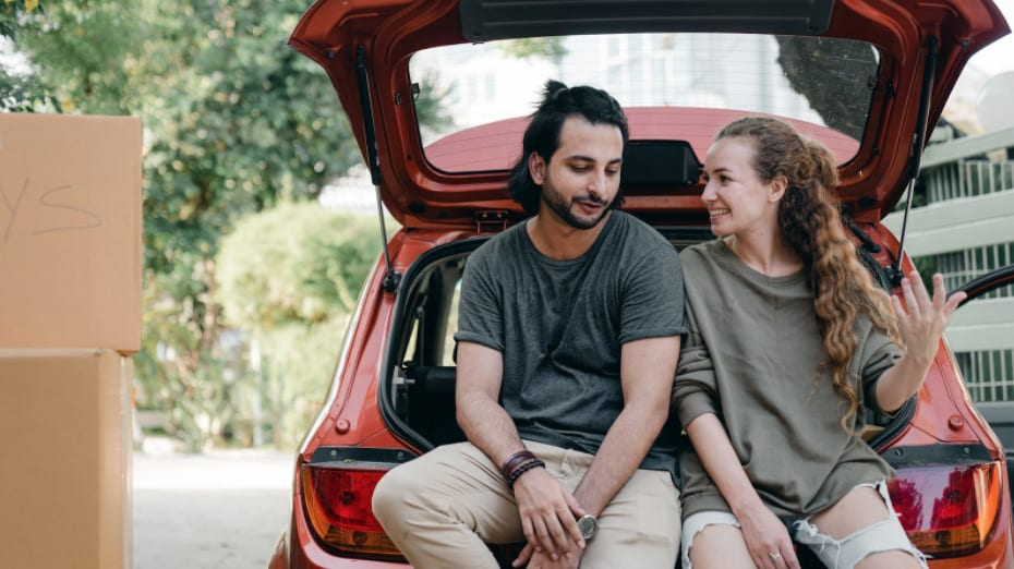 Couple in love sitting on car